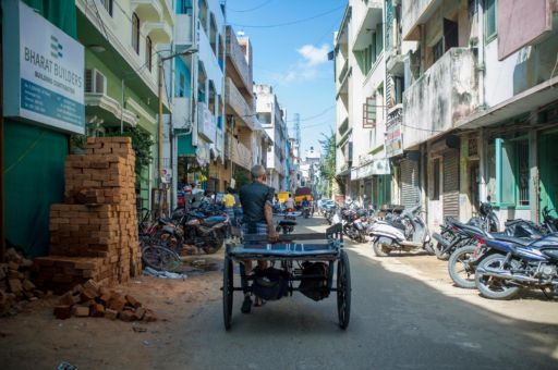 Philippe pulls his cart through the Chennai backstreets to collect goods for a job.