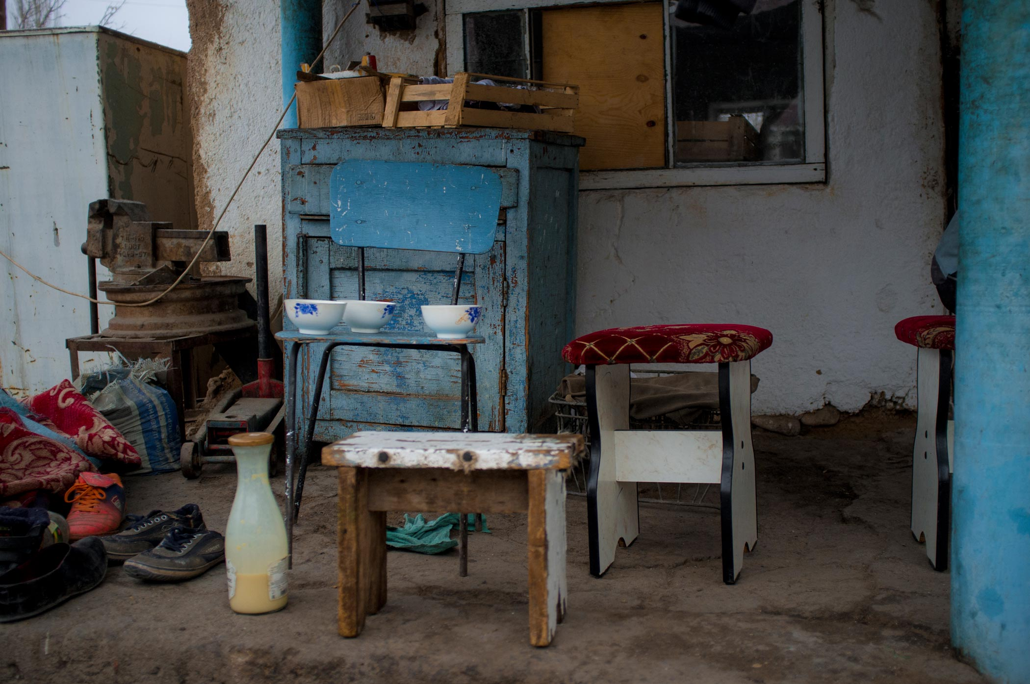 Wooden stools, bowls and a bottle of bozo outside a house in Min Kush Kyrgyzstan
