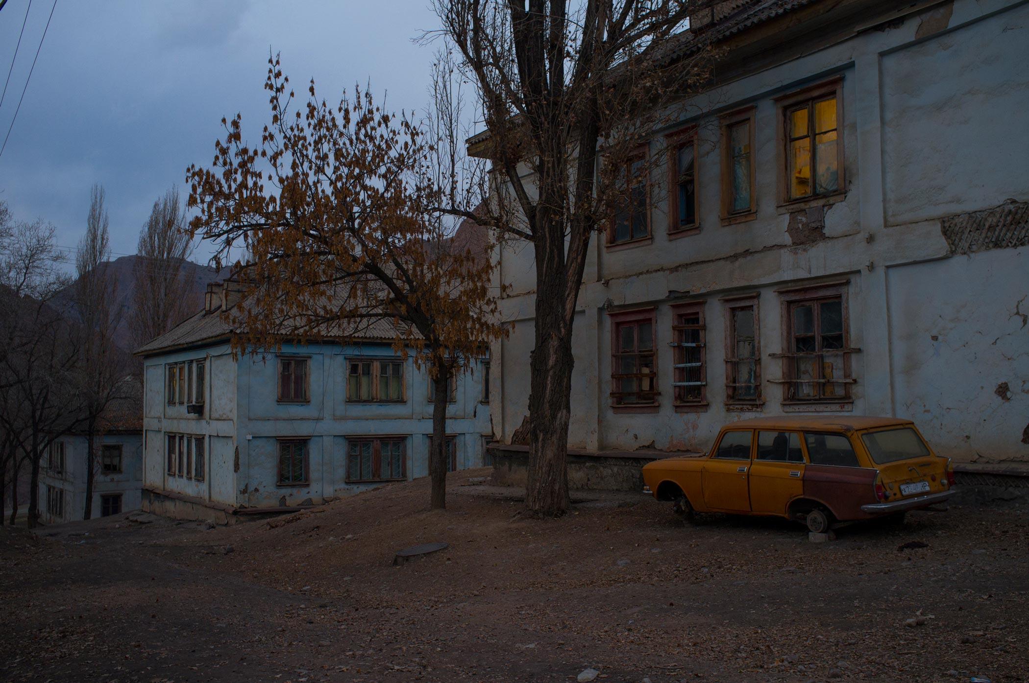 An orange car outside houses in Min Kush, Kyrgyzstan
