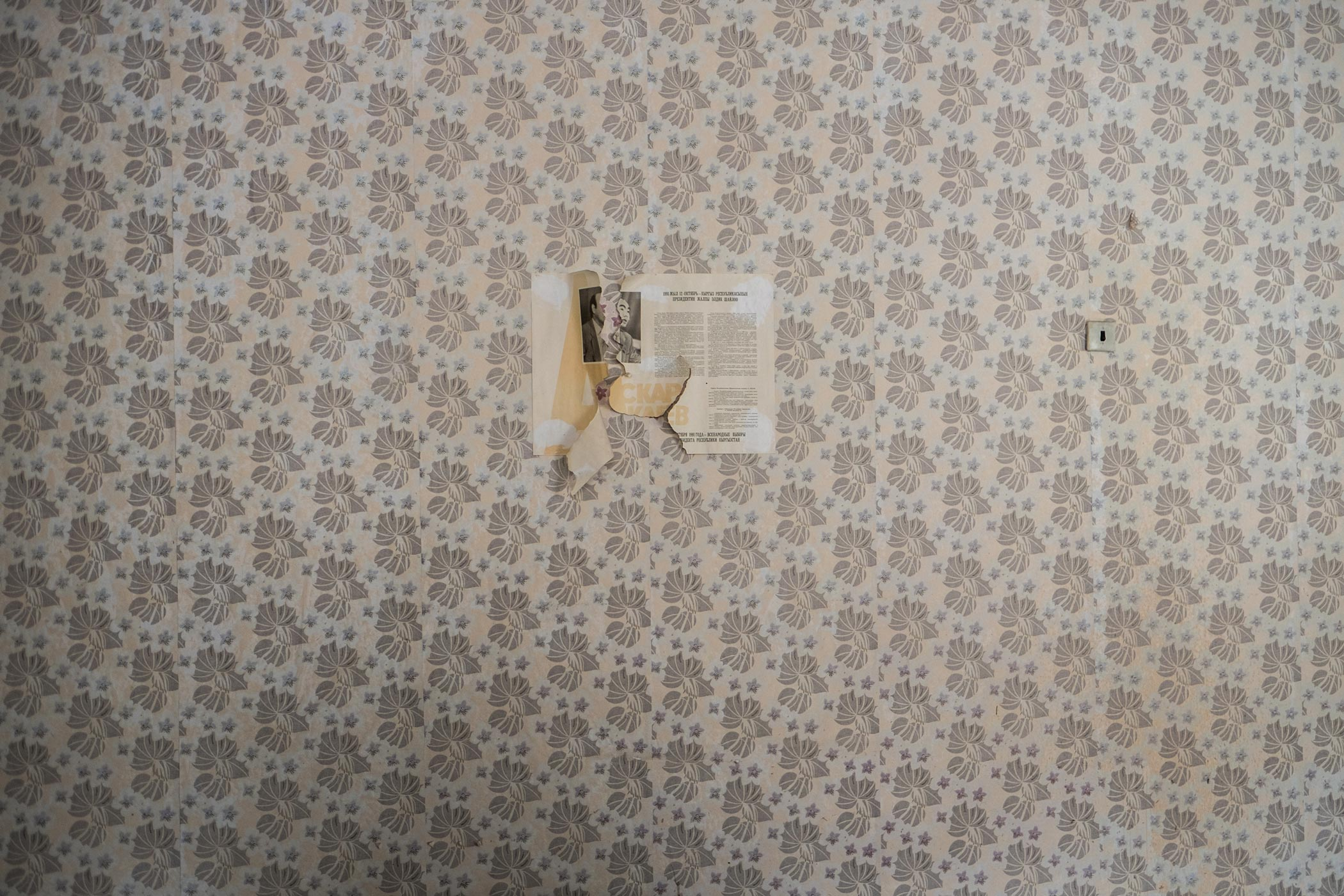A wall of faded, patterned wallpaper with a newspaper cutting pasted on it in Min Kush, Kyrgyzstan