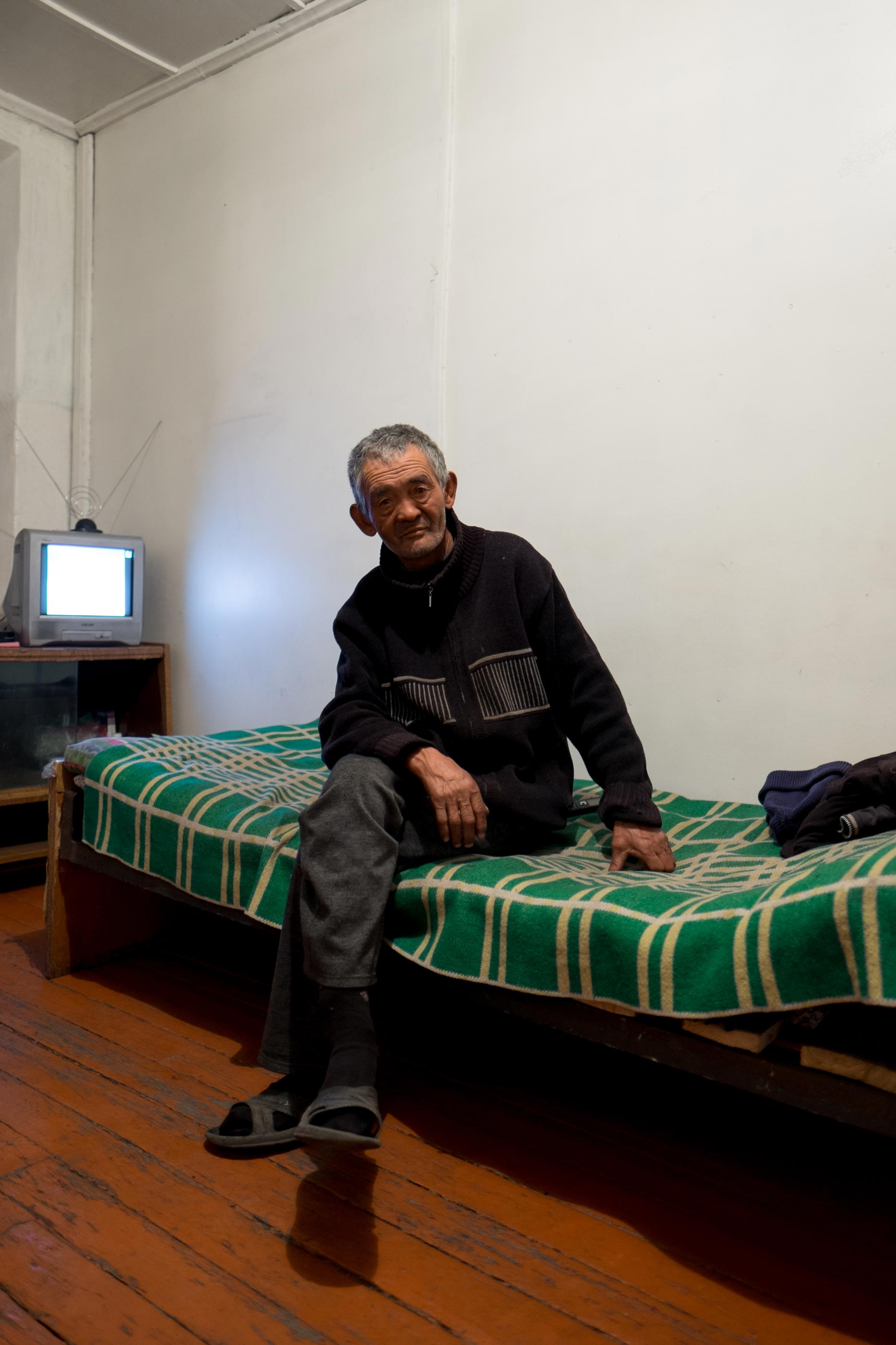 A man sits on a bed in a room in Min Kush, Kyrgyzstan