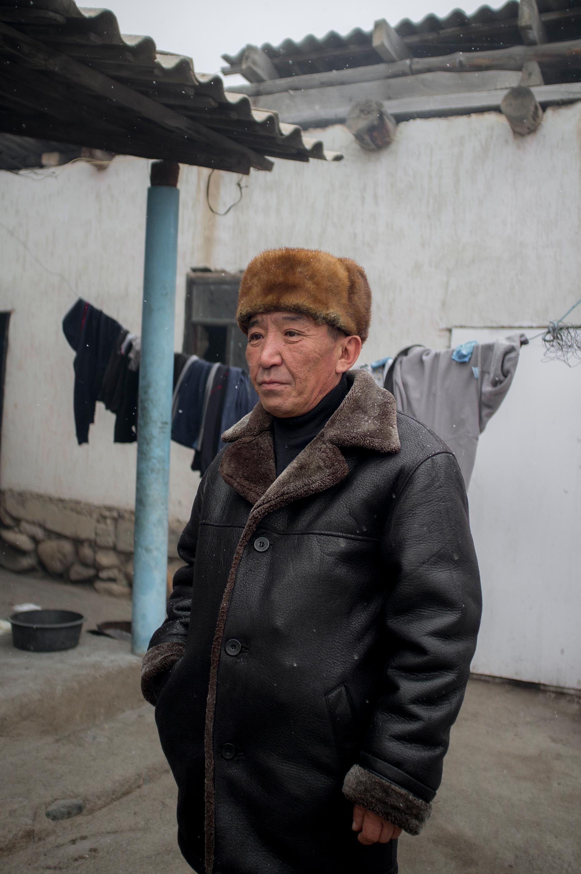 A Kyrgyz man stands in a yard in Min Kush, Kyrgyzstan