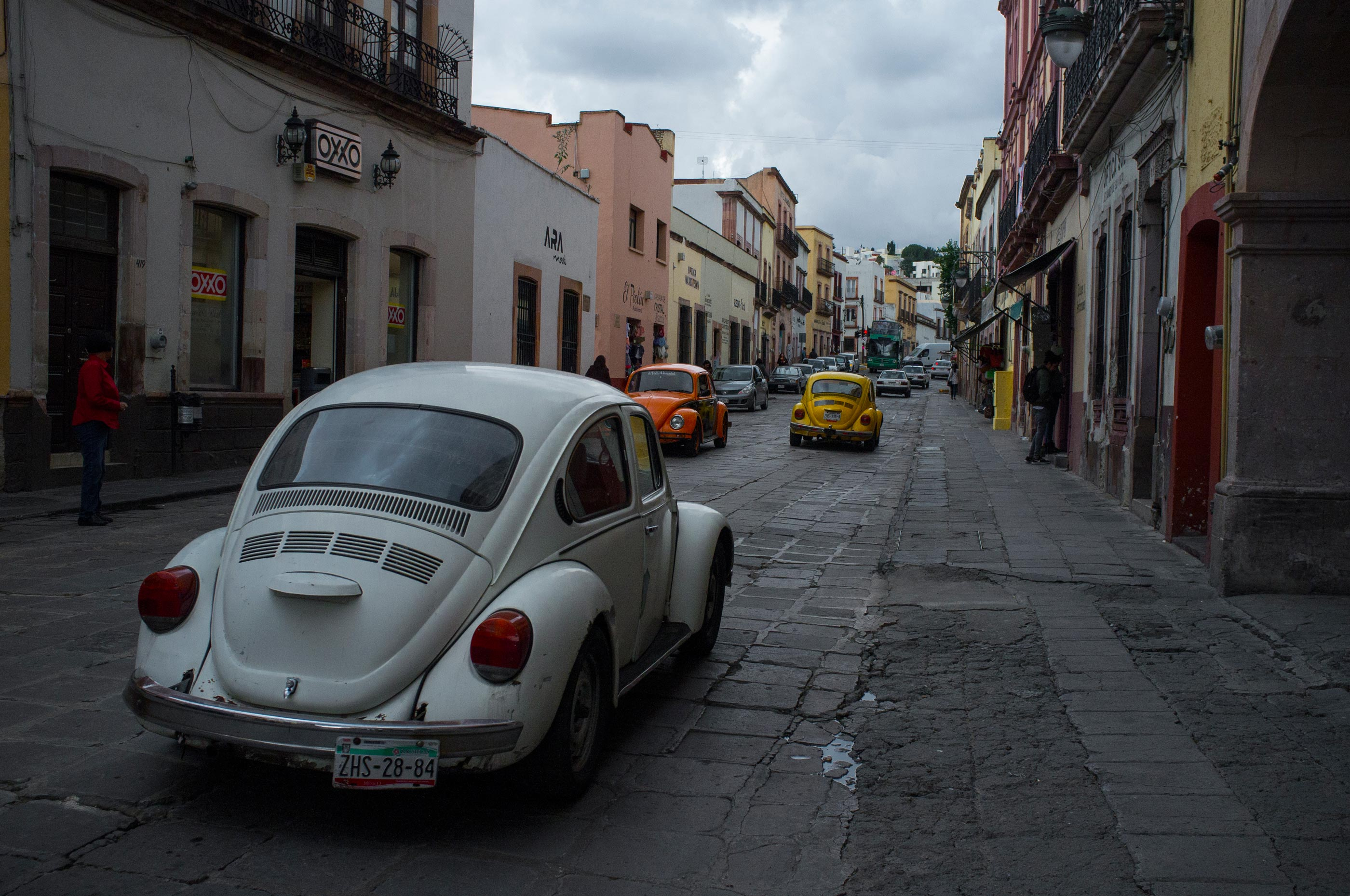 White, yellow and orange VW Beetle cars drive down a cobbled street.