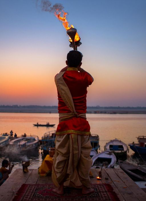 A ceremony being performed at sunrise by the Ganges.