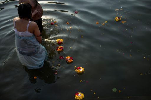 A couple takes an early morning dip in the river Ganges amongst flower offerings.