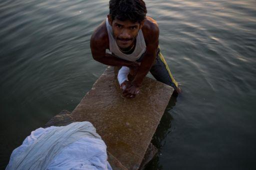 Dhobis man doing laundry on the ghats of Varanasi.