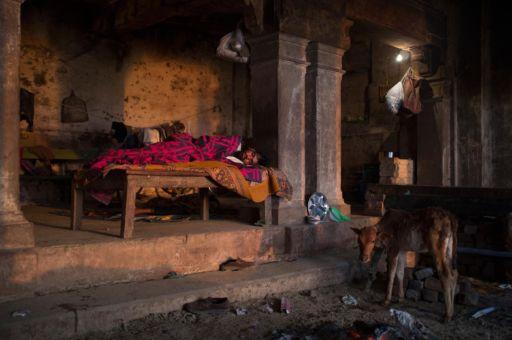 A man sleeps in a building in Varanasi.