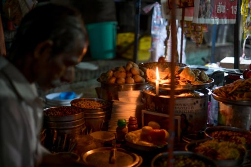 A street vendor works by candlelight to make snacks in Varanasi.