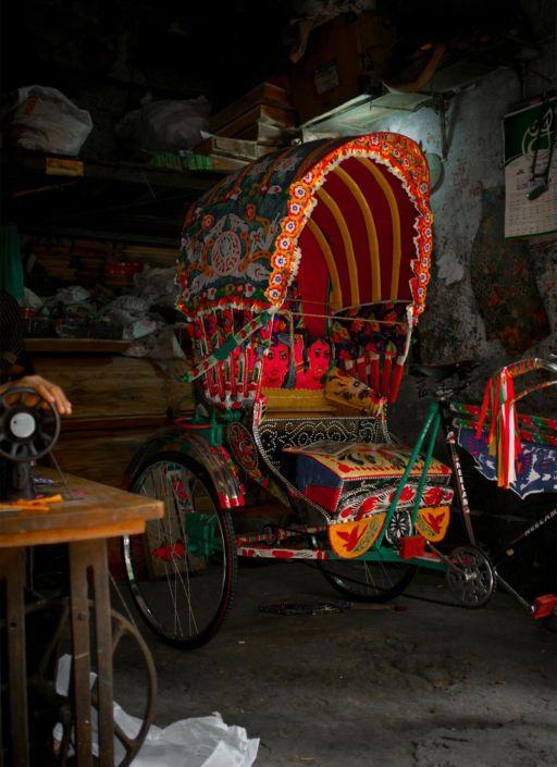 A brand new, freshly painted rickshaw in a Dhaka workshop.