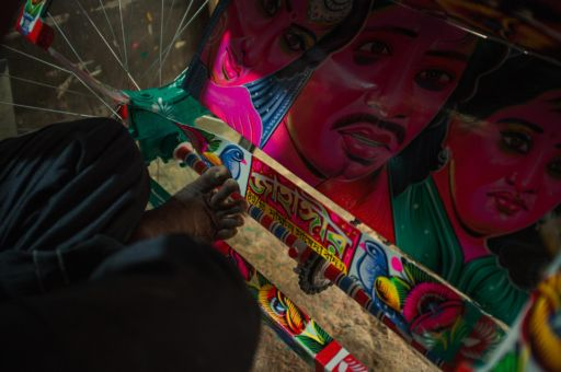 A rickshaw artist paints final details onto a rickshaw