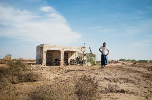 A supervisor at a salt pan in Rajasthan stands outside a small white hut.
