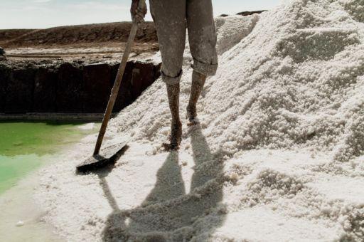 A salt worker stands in a mound of harvested salt in Rajasthan.