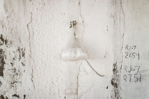 A small bag of salt hand from a white wall in Rajasthan.