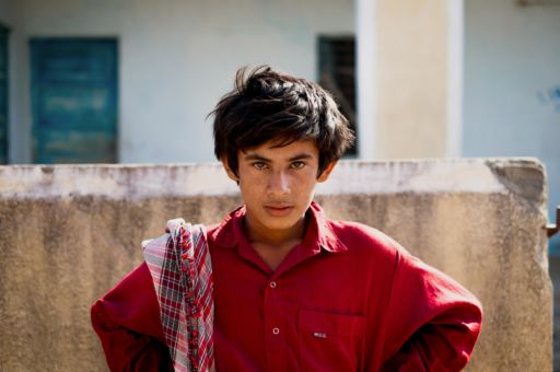 A boy stands outside his house in a village in Kutch, Gujarat.