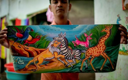 Yousuf, a Dhaka rickshaw artist, holds one of his paintings.