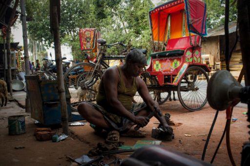 A rickshaw mechanic outside a workshop in Rajshahi.