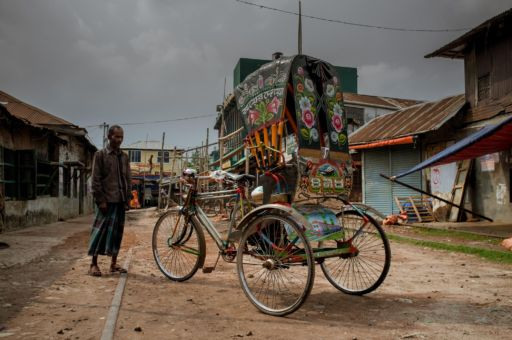 A rickshaw puller with his rickshaw in Khulna, where planes and trains are the decorative order of the day.