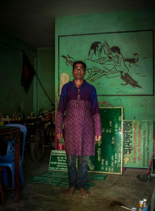 Bulbul, a former rickshaw artist in his studio in Srimangal in front of a mural on his wall.