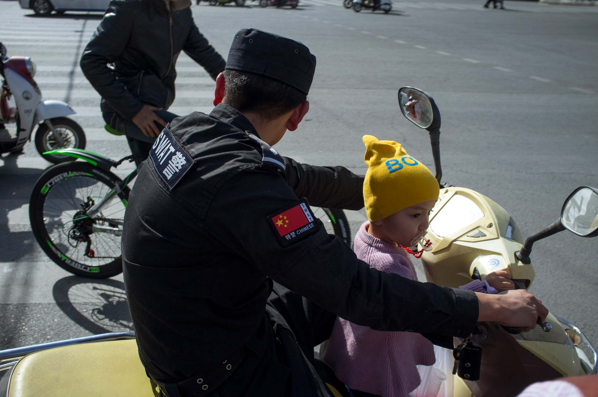 A police man rides a scooter with his daughter in Xinjiang