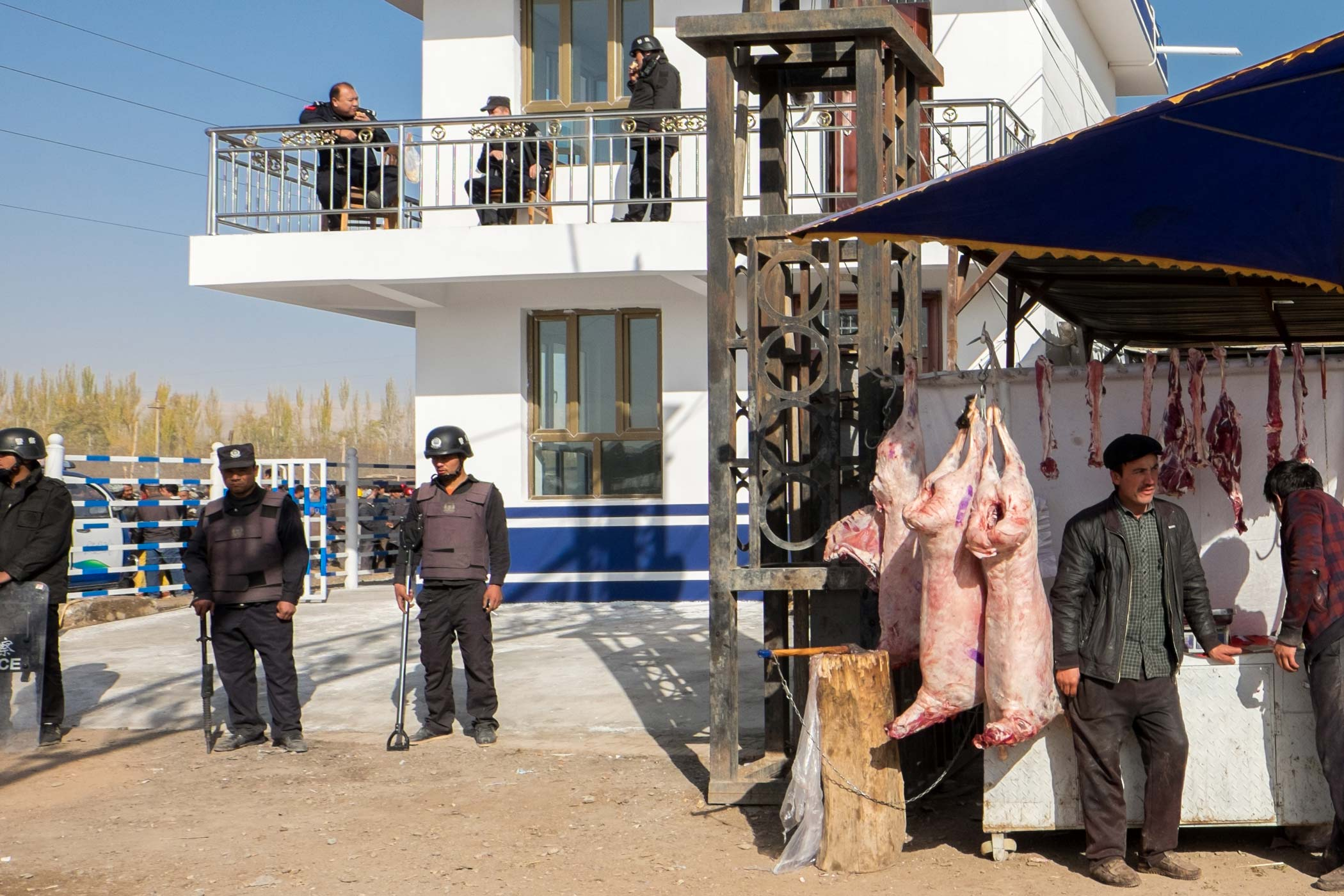 Police stand guard next to a meat stall in Kashgar, Xinjiang.
