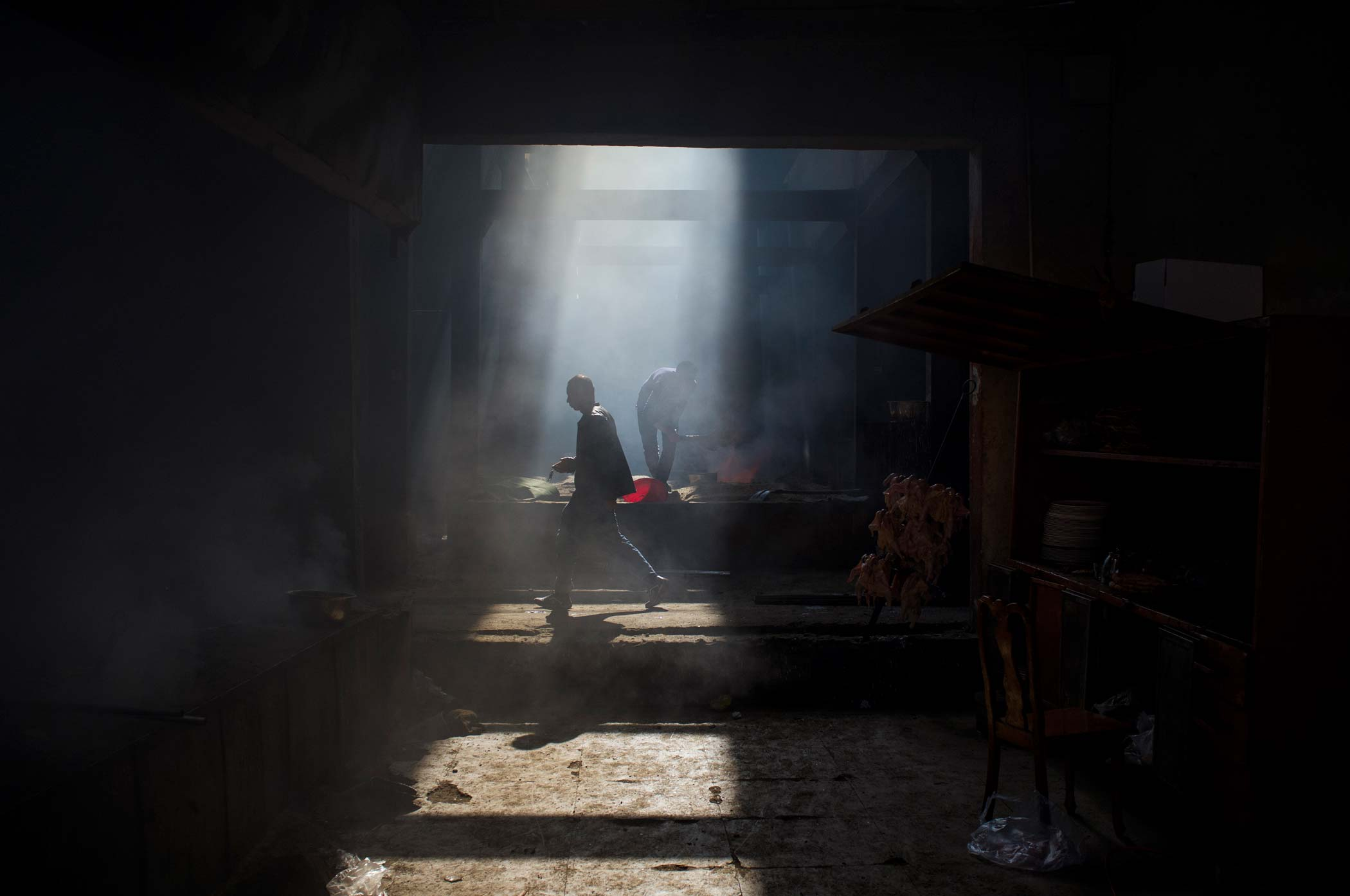 A man walks across a shaft of light in a kitchen in Hotan.