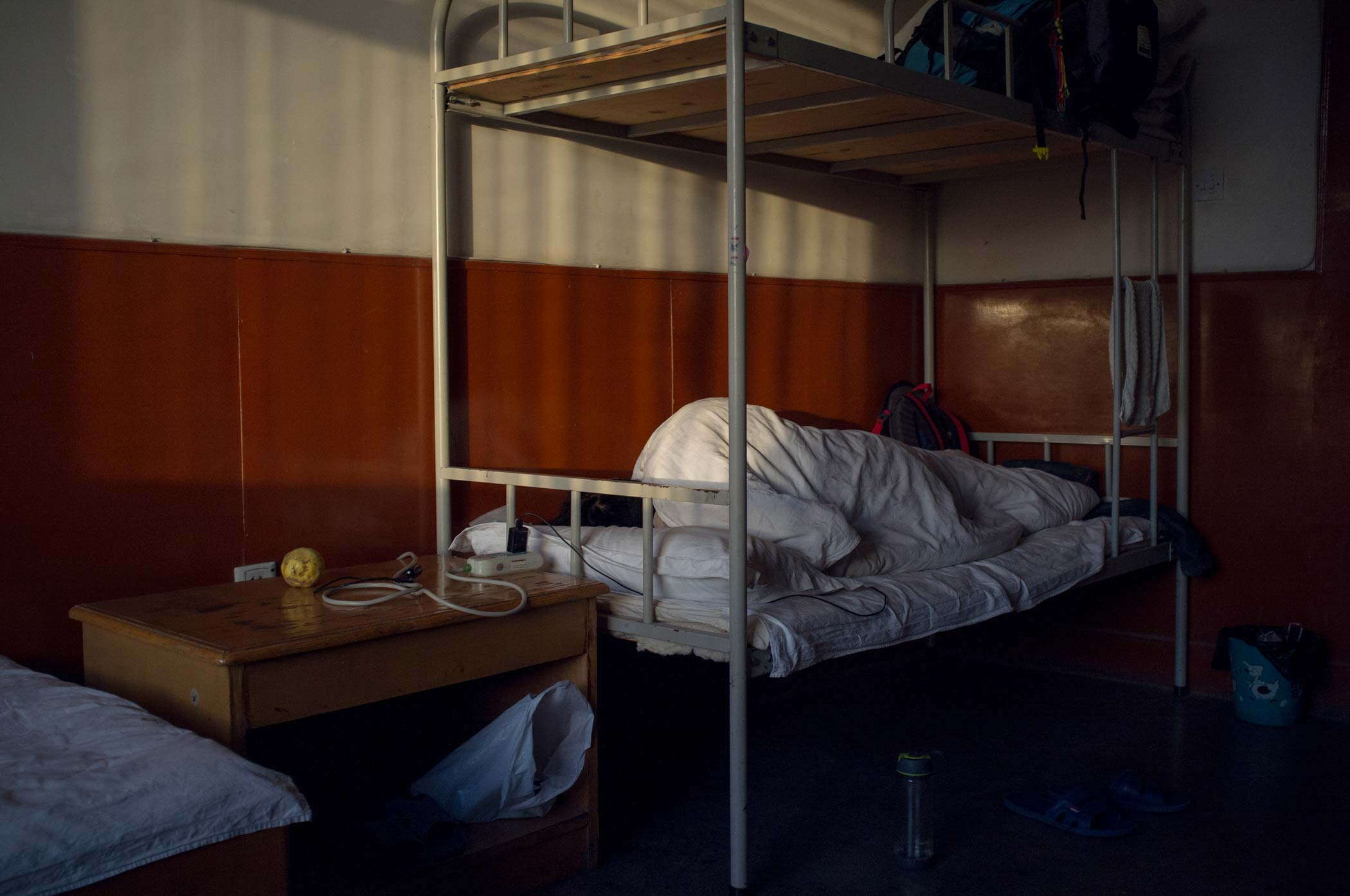 A man asleep in a dormitory bed in Xinjiang, China