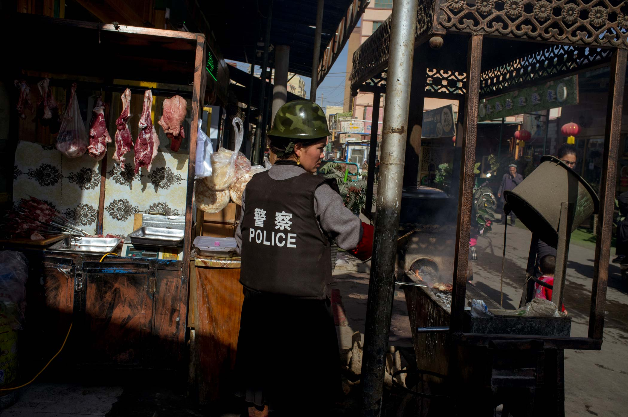 A street vendor in Xinjiang, China, wearing a police vest and helmet