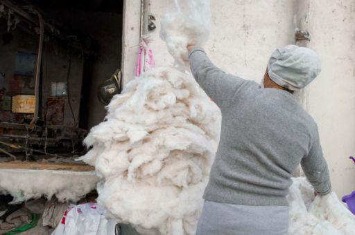 A woman sorts sheeps wool in Xinjiang, China