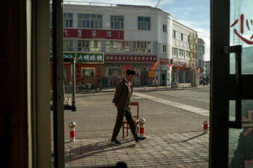 A Tajik man walks past a doorway in Tashkurgan, Xinjiang.