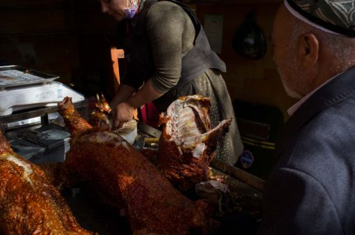 A woman sells roasted lamb at a stall in central Hotan.