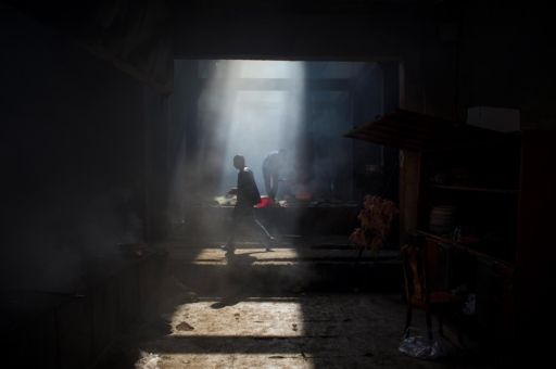 Men stand in a smoky room, prepping chickens to be roasted in Hotan, Xinijang.