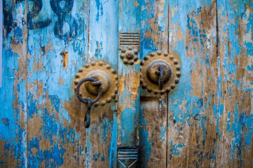Gold door handles on a chipped blue door in Yarkand, China