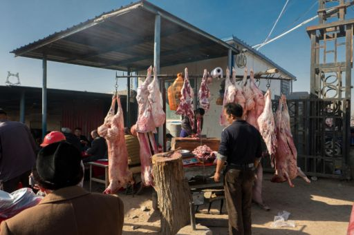 Freshly slaughtered lamb hangs for sale at a market in Kashgar.