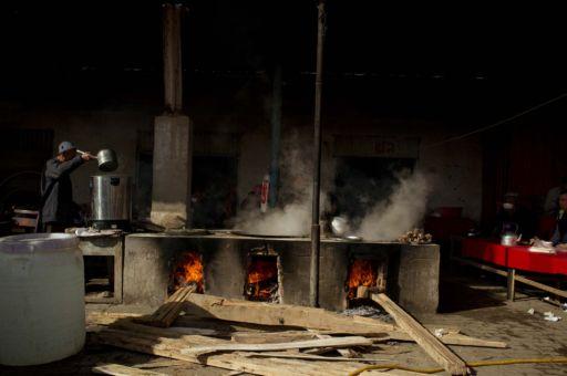Vendors cook meat stews over book burning stoves in Kashgar.