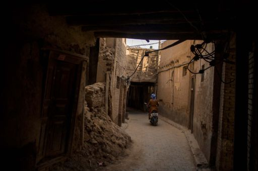 A woman on a scooter rides down a dusty alleyway in Kashgar Old City.