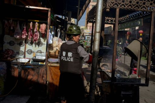 A food stall holder in Xinjiang, China, wearing a police flak jacket.
