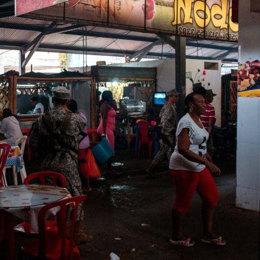 A soldier stands amongst customers at the Galeria Pueblo Nuevo market in Buenaventura, Colombia.