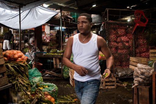A man in a white vest walks through a market in Buenaventura, Colombia