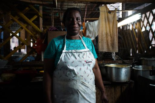 A woman in an apron stands in a market kitchen.