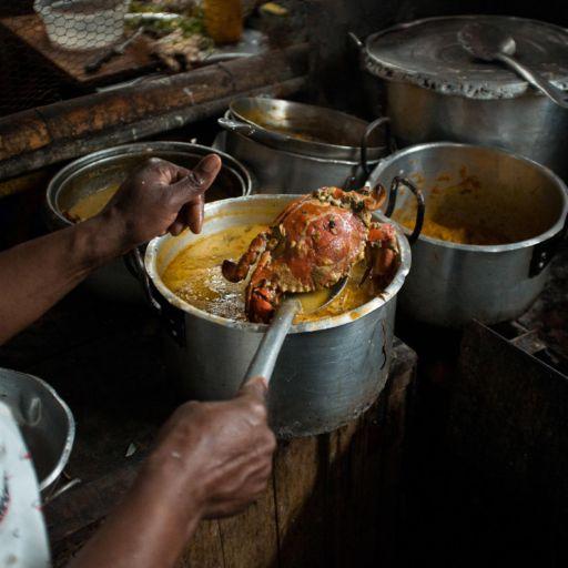 A woman's spoons a crab out of a saucepan in the Galeria Pueblo Nuevo market in Buenaventura, Colombia.