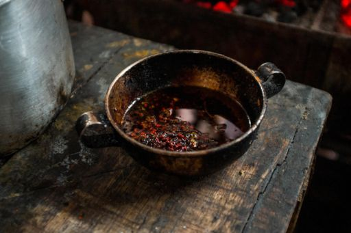 A small pan of fried achiote seeds on a sideboard in the Galeria Pueblo Nuevo market, Buenaventura, Colombia.